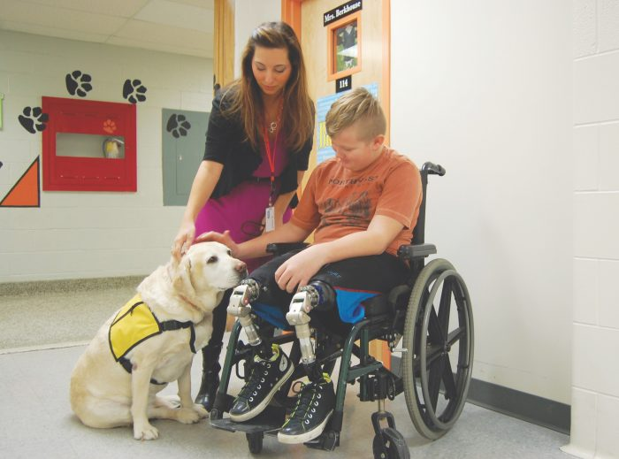 A fifth-grader who recently started using prosthetic legs visits with Bella at Green Intermediate School in Ohio. Her presence promotes feelings of safety among students, says her owner.