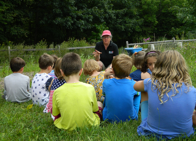 "Ingrid Zabel, an author of ""Teacher-Friendly Guide to Climate Change,"" speaks to children at the Cayuga Nature Center in Ithaca, New York, about how climate change is altering animal habits."