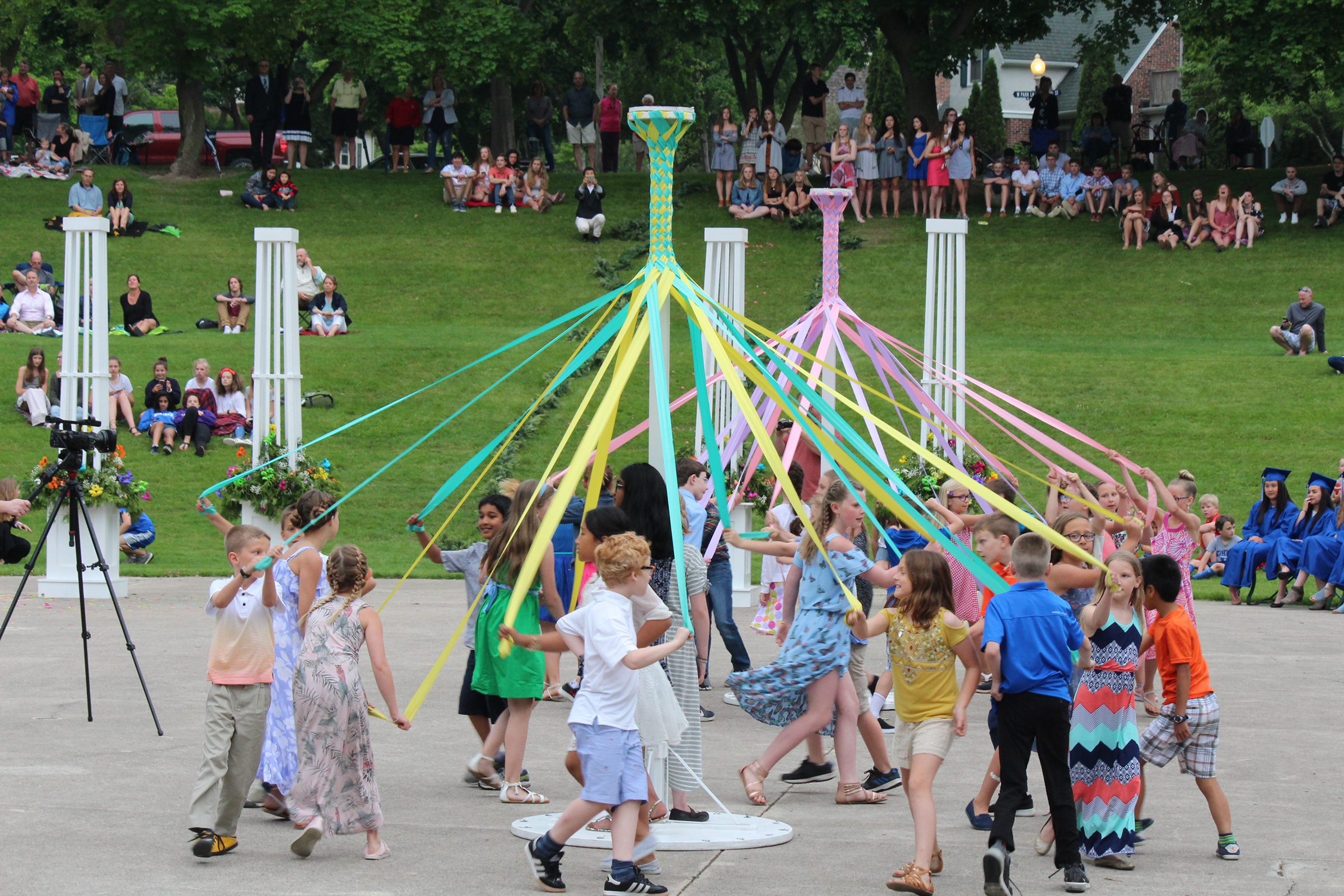 Elementary school students dance around a maypole in a local park during Kohler's high school graduation ceremony—a tradition that also includes a procession through the village and a group dinner.