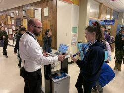 Mr. Kirkman, principal of Riverside Middle Schools, checking a student's grades so she can enter study hall.