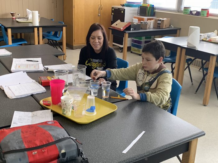 Mrs. Mathison redoing a science lab for a student who was absent the day of the lab.