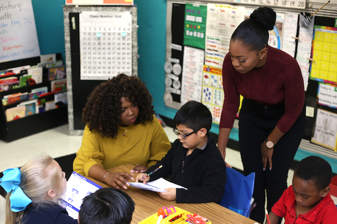 Dallas Teacher Residency program student Cynthia Fitz-Wilson (in yellow) works with kindergarten students under the guidance of mentor teacher Chaslyn Reynolds (in maroon) at Ben Milam Elementary School in Dallas ISD.