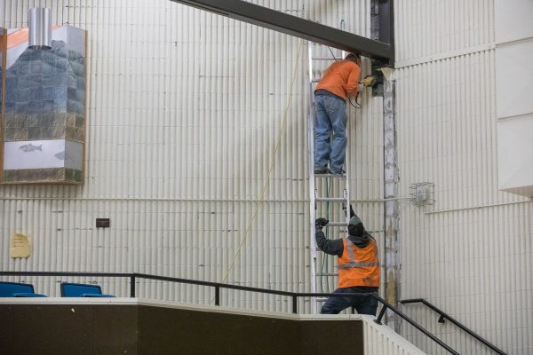 Workers remove damaged concrete siding inside Gruening Middle School (pictured) in Eagle River, Alaska, after an earthquake last year.