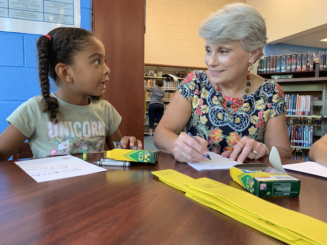 Hoover City Schools Superintendent Kathy Murphy and an elementary school student discuss their arts and crafts assignment in the library.