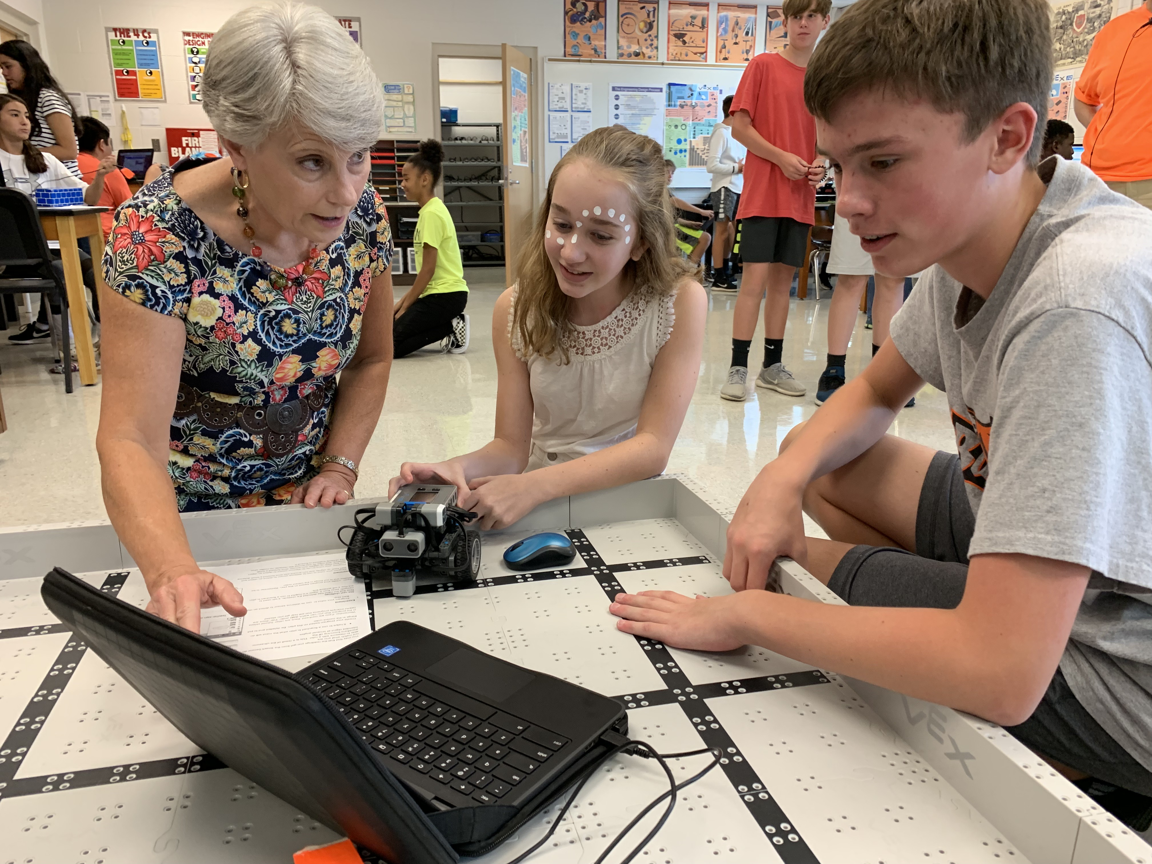 Two students tell Superintendent Kathy Murphy about the code they are writing and the tasks they want their robot to accomplish.