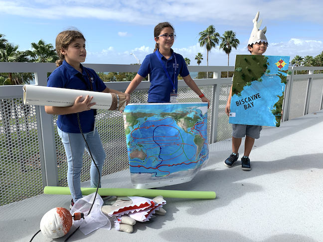 Students at Miami's MAST Academy show off a science project, with the waters of Biscayne Bay behind them.
