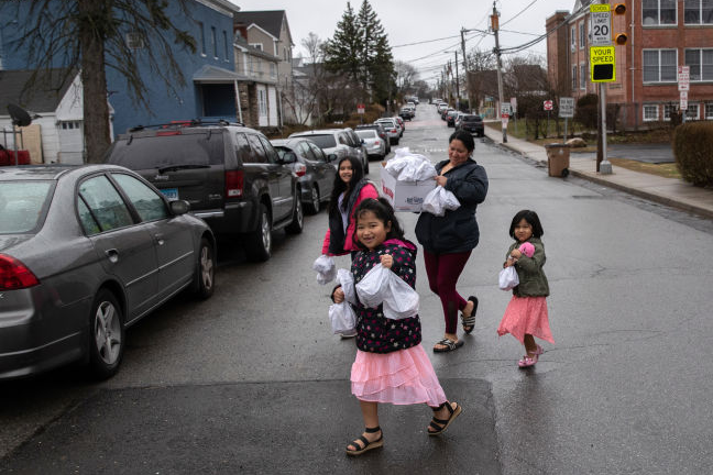 In many communities with school closures, free bagged meals are distributed to families at pick-up sites such as this one in Stamford, Conn. Photo by John Moore/Getty Images