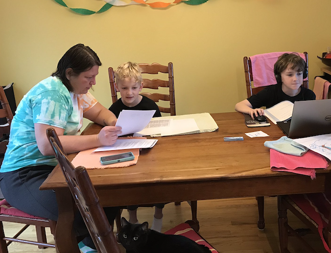 A parent and her children work on online learning assignments during coronavirus school closures in Hamilton County, Tennessee.