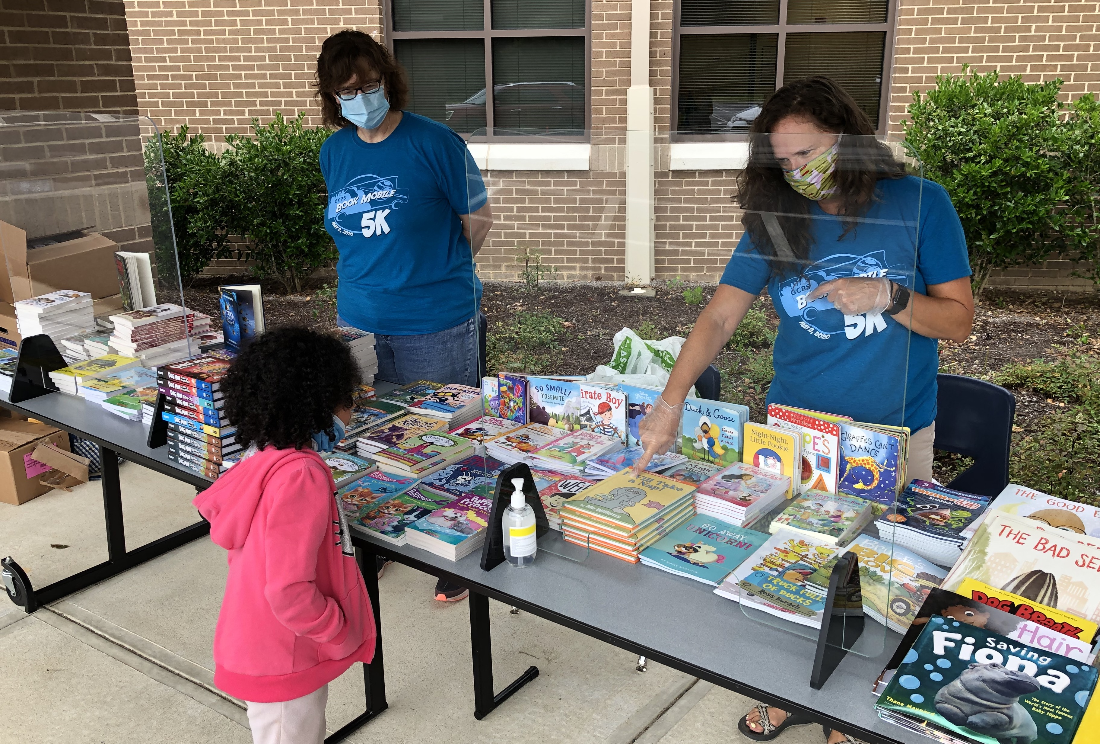 Gwinnett County Public Schools media specialists offer two new books to a student as part of the district's Books 2 Kids program that will run throughout the summer to encourage reading at home.