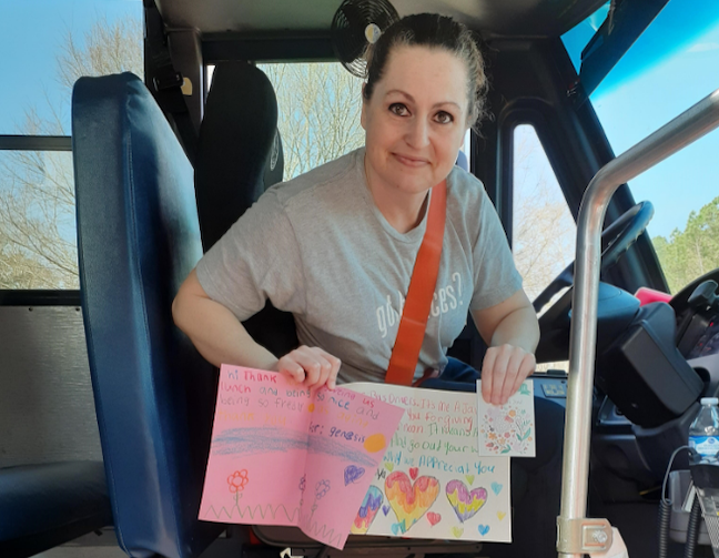 A Gwinnett County Public Schools bus driver who deliver meals while classrooms were closed shows off thank you cards she received from students.