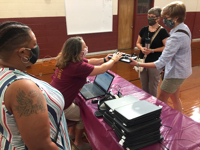 Educators in Newport News Public Schools distribute laptops this summer for online learning.