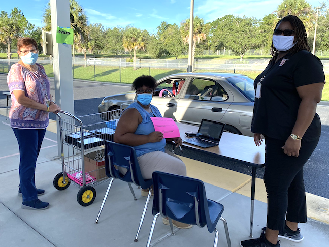 Educators at Orange County Public Schools in Florida prepared laptops to distribute to students for online learning.