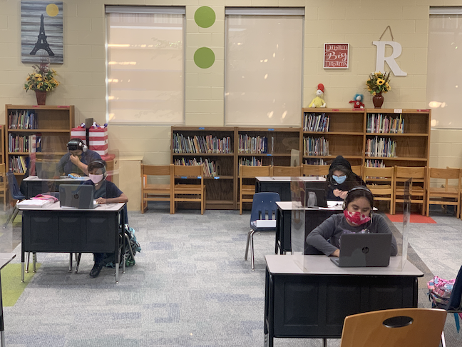 Mask-wearing students are social distanced and protected by plexiglas shields in Pharr-San Juan-Alamo ISD in Texas.