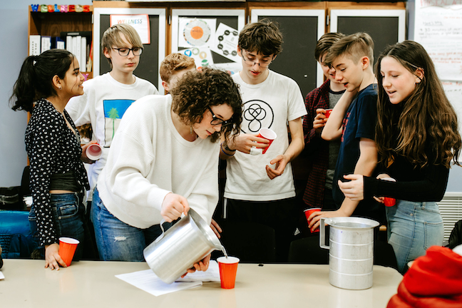 Students choose between two pitchers of identical-looking beverages to learn about 'drug checking' as a harm reduction practice.