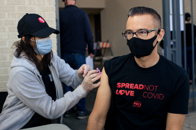 Phoenix Union High School District Superintendent Chad Gestson gets vaccinated at one his district's buildings.