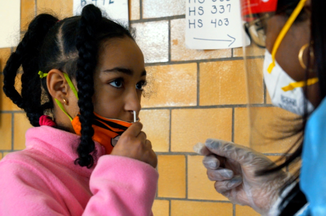 A student swabs herself as part the pool COVID testing initiative expanding to schools statewide in Massachusetts.