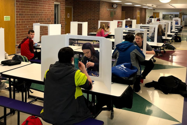 Students eat lunch separated by dividers in Wisconsin's School District of Waupaca.